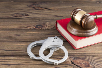 hammer of a judge, book, handcuffs on a wooden background. law. jurisprudence. criminal law