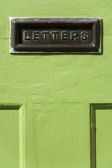 Old mail letter box in a distressed green house front door