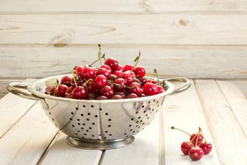 Metal colander full of freshly cherries over a rustic board.