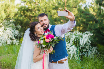 Groom make photo with his bride outdoors
