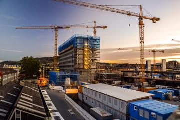 Baustelle am Abend, Neubau mit Baukran bei Sonnenuntergang