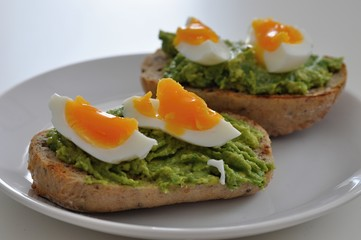 cereal bread with avocado spread and egg on white plate, healthy breakfast, vegetarian food