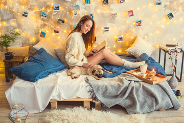 Young woman weekend at home decorated bedroom stroking dog reading book