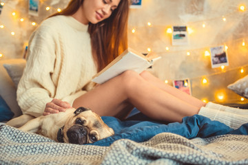 Young woman weekend at home decorated bedroom with dog close-up