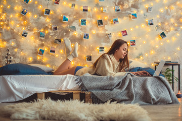 Young woman weekend at home decorated bedroom using laptop