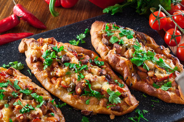 Traditional Turkish pide with meat and vegetables