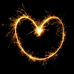 Sparkling golden heart isolated on black background