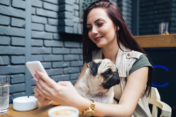 Beautiful woman with her pug dog in cafe bar.