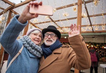 Joyful mature married couple is making selfie on street. Woman is holding smartphone and smiling. Man is waving arm to camera. Winter holiday entertainment concept