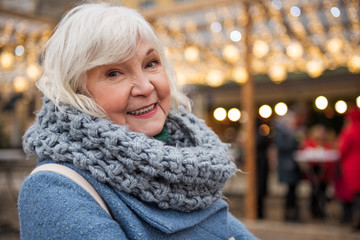 Portrait of excited senior woman enjoying winter holidays on street. She is looking at camera and smiling. Copy space