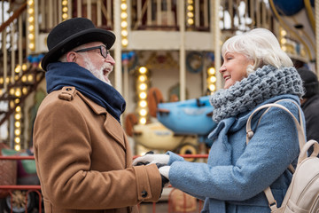 Enjoying romance in any age. Happy mature loving couple is holding hands while standing on street. They are looking at each other with gentleness and smiling
