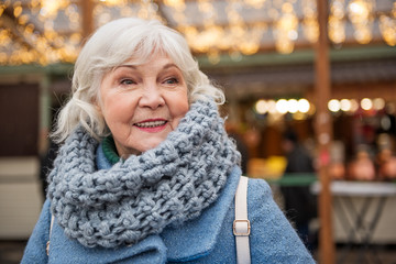 Portrait of happy old woman standing on street and smiling. She is wearing warm coat and scarf