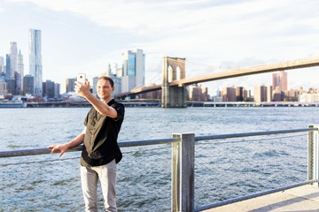 Young man outside outdoors in NYC New York City Brooklyn Bridge Park by east river, railing, looking at view of cityscape skyline, taking selfie with smart phone
