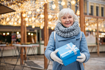 Waist up portrait of happy senior woman giving present with generosity. She is standing outdoor and smiling. Holiday concept. Copy space