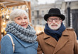 Portrait of cheerful mature married couple relaxing in city. They are looking at camera and smiling