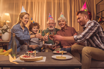 Cheerful family drinking glasses of champagne and eating cake while situating at table. They celebrating birthday. Festivity concept