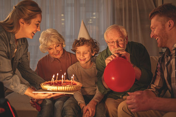 Outgoing mother giving cake with candles to cheerful son. Beaming grandmother sitting near him. Grandfather inflating balloon. Happy birthday concept
