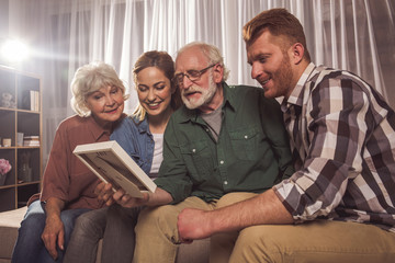 Happy granny with beaming lady and outgoing grandfather with man looking at frame in apartment. Memory concept