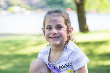 Close-up,Portrait of Beautiful Cute Adorable Little Five Years Old Girl with Big Eyes and Brown Hair PonyTail, Outdoors,in Park Sunny Summer Day,Blue Lake Park Troutdale OR USA, Funny Face Expression