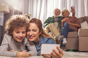 Portrait of happy female and smiling kid taking selfie by mobile while locating on carpet. Beaming grandparents drinking cup of tea and sitting on sofa. Entertainment concept