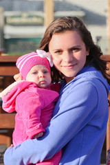 Close-up Portrait of Very Beautiful Teenage Girl with Long Brown Hair and Big Eyes looks at Camera Holding Her Sister baby Girl in Pink Outfit, Sunny Day, Oregon USA