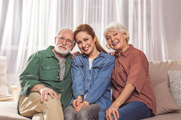 Portrait of cheerful bearded grandfather sitting near glad daughter and outgoing wife on sofa. They looking at camera. Care concept