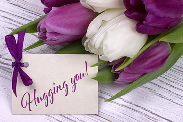 Valentines day greeting card, tulips white purple ribbon, white wooden background.