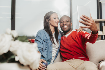 Smile. Content espoused man and woman sitting on cozy sofa and taking photo of themselves. Copy space in left side