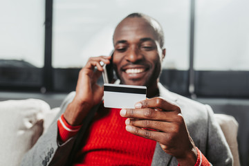 Portrait of smiling guy sitting on couch and communicating by cellphone. Focus on bankcard in his arm