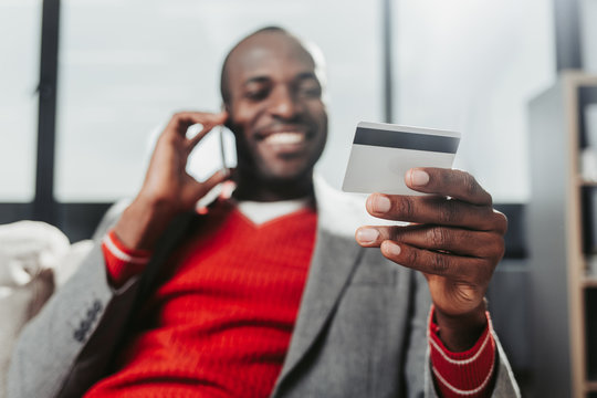Low angle portrait of delighted man chatting by mobile phone at home. Focus on hand holding credit card