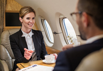 Portrait of smiling elegant female in airplane. She is drinking tea and talking to man sitting in front of her. Focus on lady