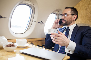 Tranquil solid businessman sitting in first class seat of airliner, he is talking by cellphone and gesticulating