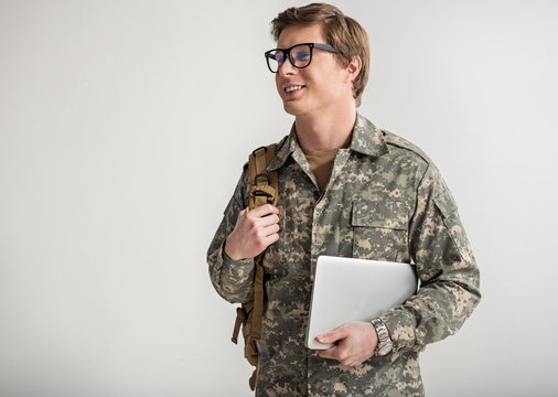Pleased young male cadet smiling and holding laptop. He is having rucksack on shoulder and wearing eyeglasses. Isolated on background. Copy space in left side