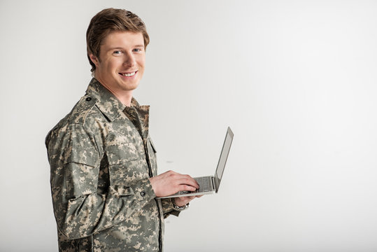 Pleased military young man looking at camera and smiling. He is having laptop in hand. Isolated on background. Copy space in right side
