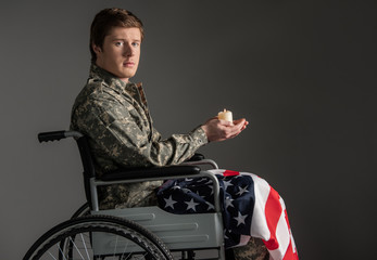 Cheerless disabled soldier looking at camera with sad look and sitting in wheelchair. He is having candle in hands and flag on his knees. Isolated on grey background