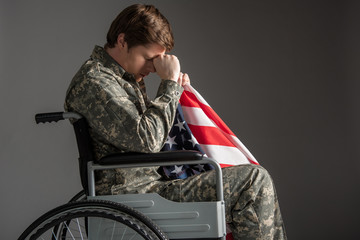 Sad disabled soldier sitting in wheelchair with upset look. He is holding usa flag and propping his head with hand. His ayes are closed. Isolated on grey background