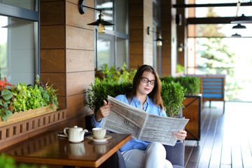 Beautiful woman resting and reading newspaper articles at restaurant  . Charming female person dressed in jeans shirt and glasses sitting in arm chair. Concept of spending free time at cafe, havin