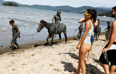 "Members of the ""Bloco da Lama"" (Block of Mud) group perform on Jabaquara beach, during a carnival festivities in Paraty"