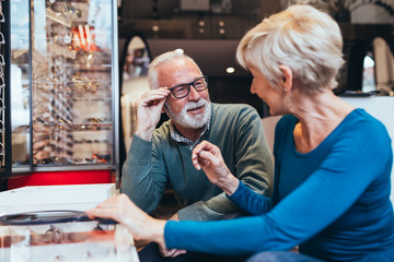 Happy senior couple choosing together eyeglasses frame in optical store.