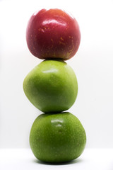 two green and one red apple stacked on top of each other