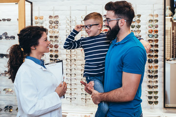 Happy father and son choosing eyeglasses frames and talking with ophthalmologist in optical store.