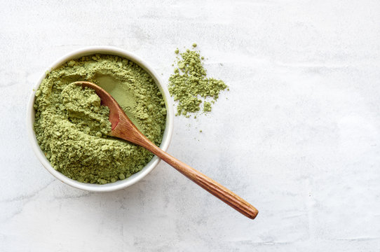Green matcha tea powder with spoon on white concrete background. Top view.