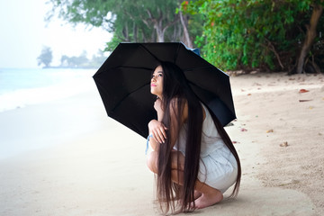 Young woman on beach holding umbrella, looking up at rain