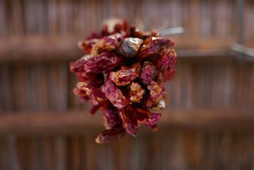 Bündel getrockneter roter Chilis von unten gesehen gegen traditionelle Decke