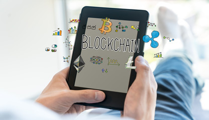 Blockchain text with man using a tablet computer