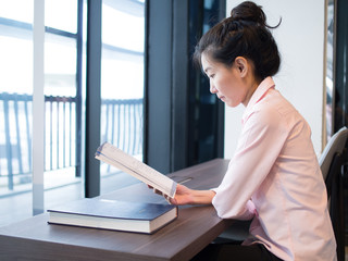 An asian female is reading books, study and research for her work.