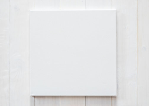White blank canvas mockup square size on white wood wall for arts painting and photo hanging interior decoration