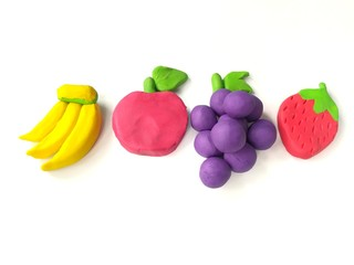 Delicious variety fruits made from plasticine clay on white background, colorful banana apple grapes strawberry dough