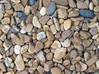 pebble stone texture background, sea stones (or river stones) for garden decor or pathway, close-up top view