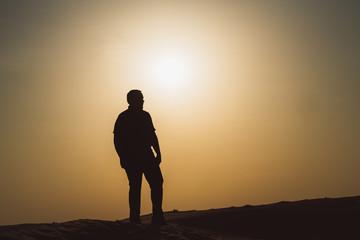 Silhouette eines Mannes bei Sonnenuntergang geht durch dich Wüste
